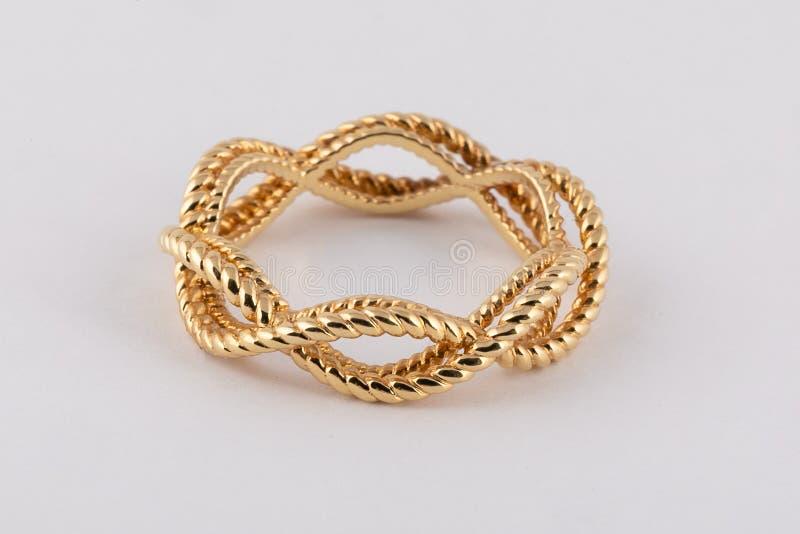 L'oro delle donne ha intrecciato l'anello isolato su fondo bianco fotografie stock libere da diritti
