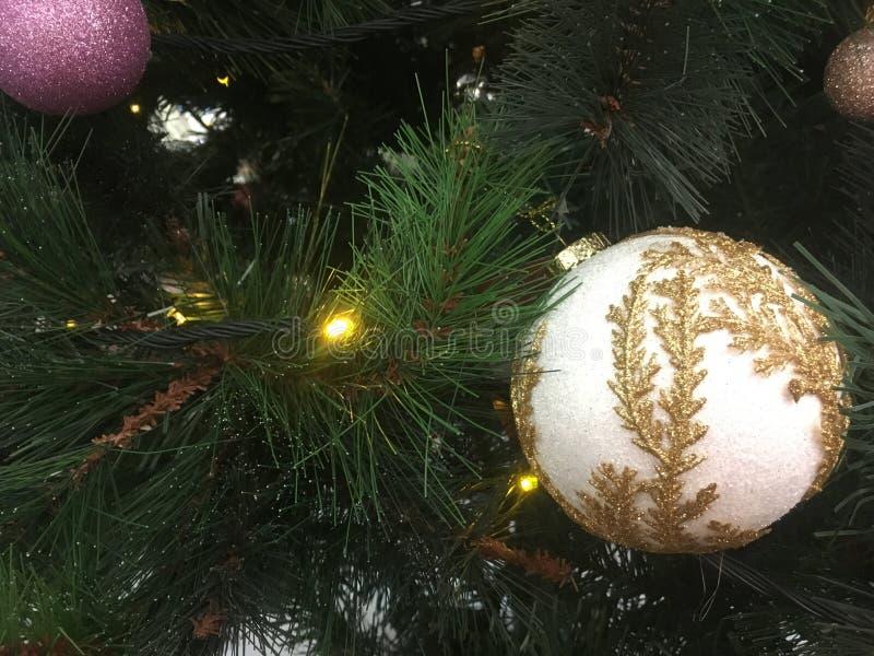L'oro ha abbellito la decorazione di Natale che appende su un albero verde fotografia stock