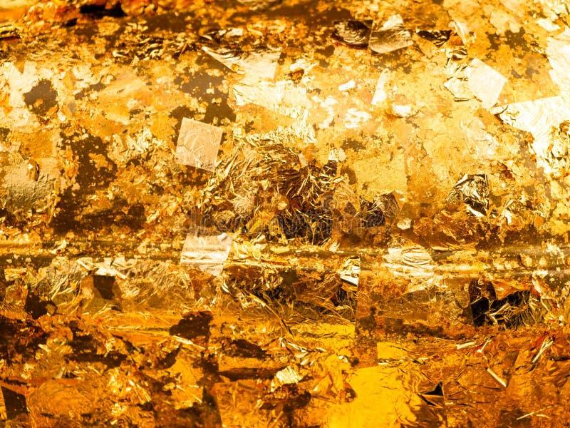 L'oro ha strutturato il fondo dai residui di stagnola immagine stock