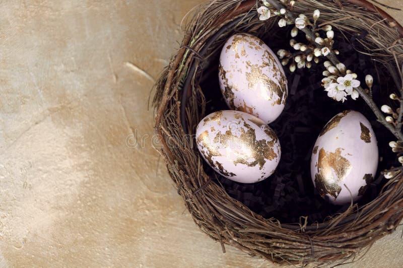 L'oro ha sventato le uova di Pasqua dipinte in un nido, decorato con un ramo del fiore di ciliegia Vista superiore, spazio della  immagini stock