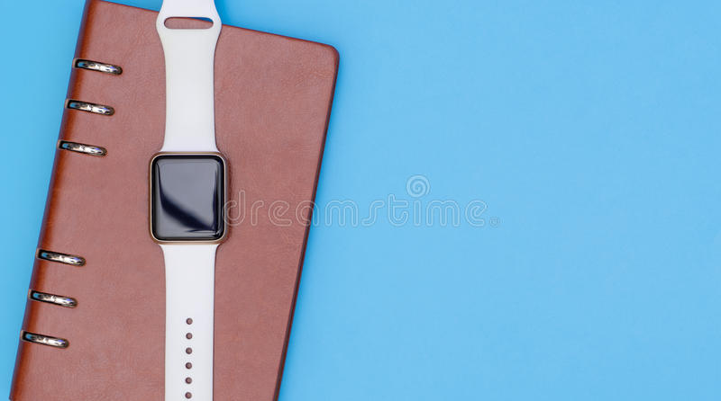 L'orologio astuto sul taccuino per organizza il concetto sul blu fotografia stock libera da diritti