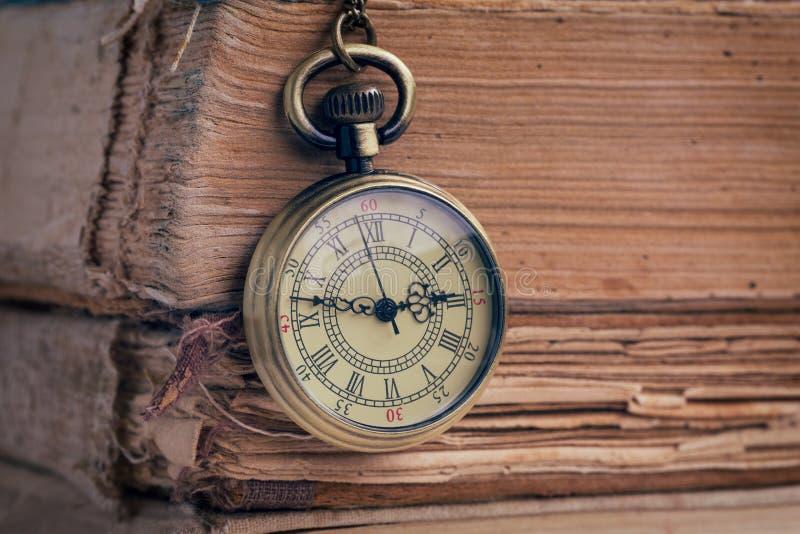 L'orologio da tasca ed i vecchi libri fotografia stock