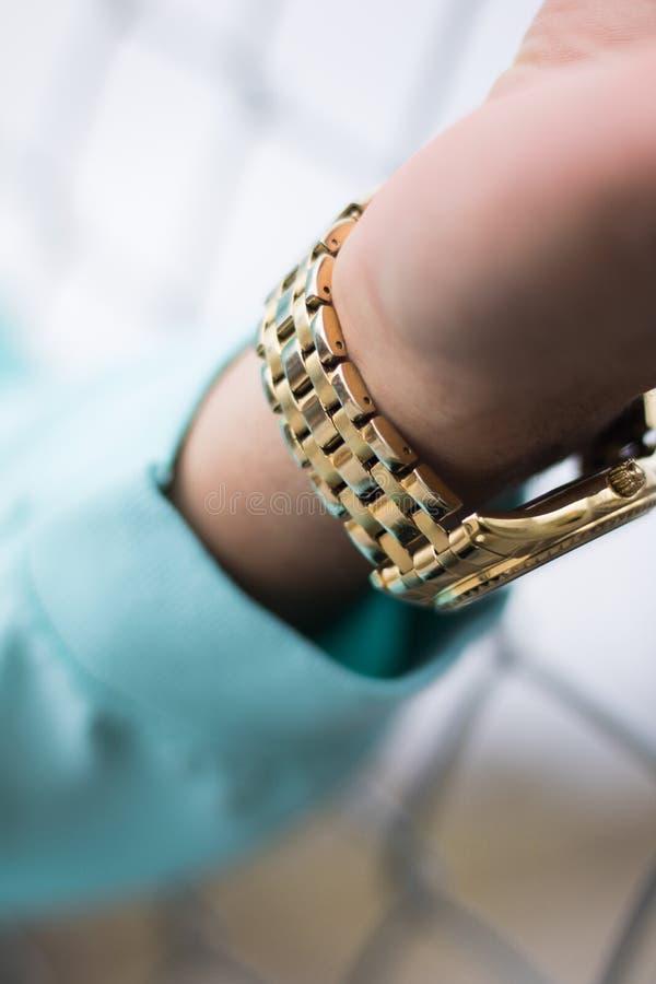 L'orologio di oro sopra equipaggia il polso fotografie stock libere da diritti