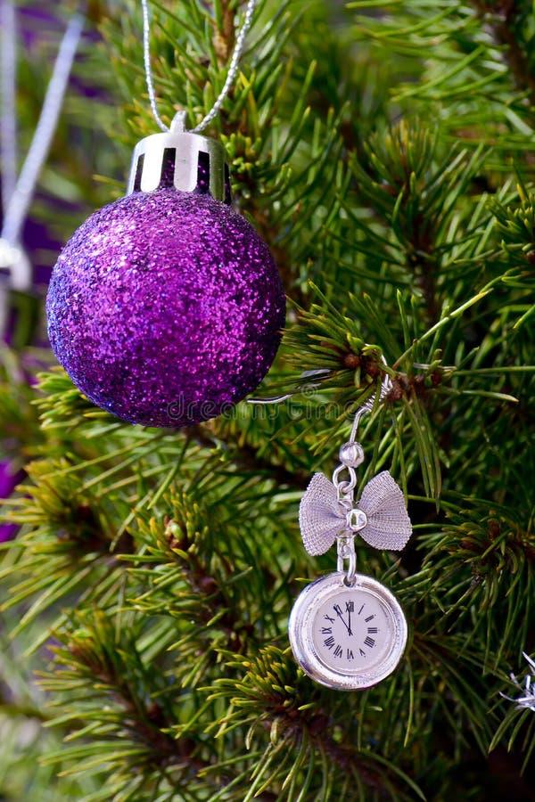L'orologio sull'albero di Natale con le palle mostra cinque minuti alla mezzanotte fotografie stock