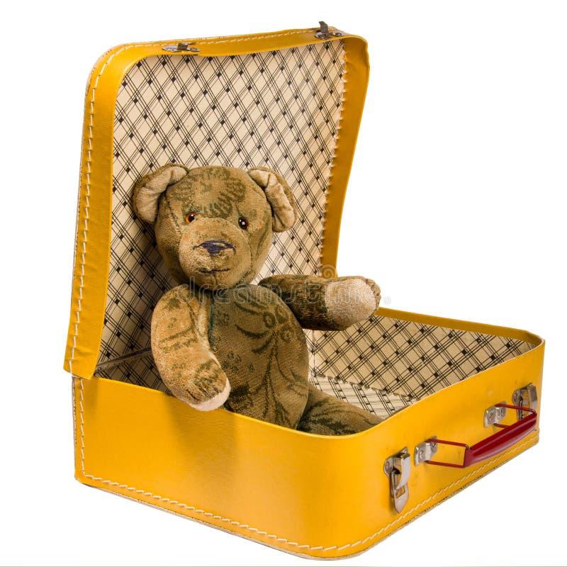 L'orsacchiotto antico che si siede in una valigia gialla vuole viaggiare immagine stock