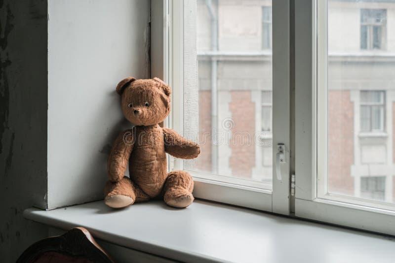 L'orsacchiotto d'annata solo riguarda la finestra immagine stock