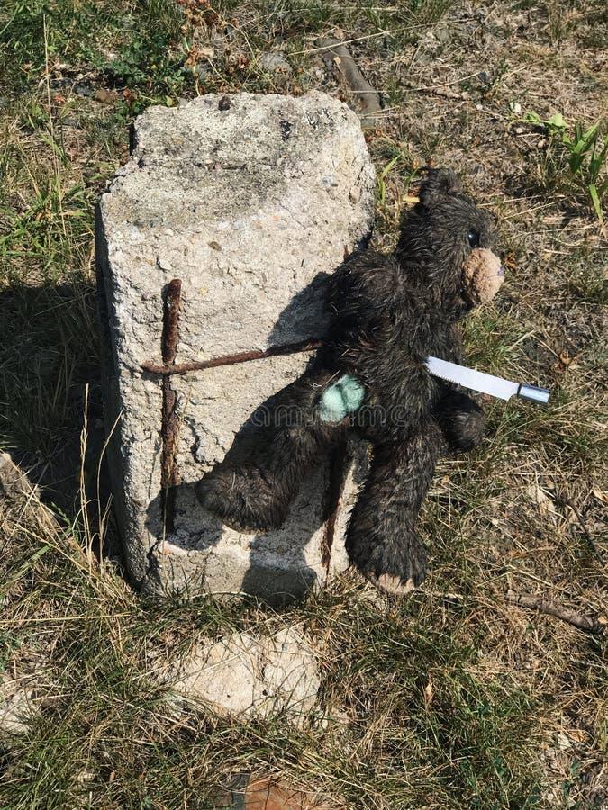 L'orsacchiotto della peluche è appuntato con il coltello alla pietra miliare immagini stock libere da diritti