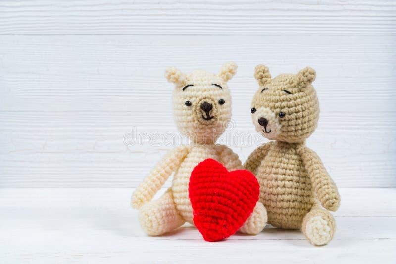 L'orsacchiotto delle coppie con cuore rosso lavora all'uncinetto tricottare fatto a mano, l'amore ed il concetto del biglietto di immagini stock