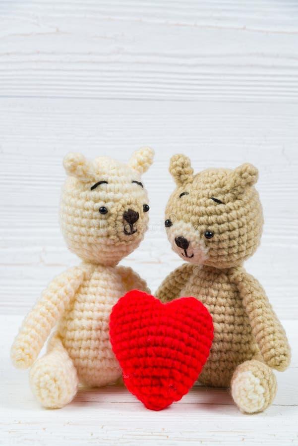 L'orsacchiotto delle coppie con cuore rosso lavora all'uncinetto tricottare fatto a mano su wh immagini stock