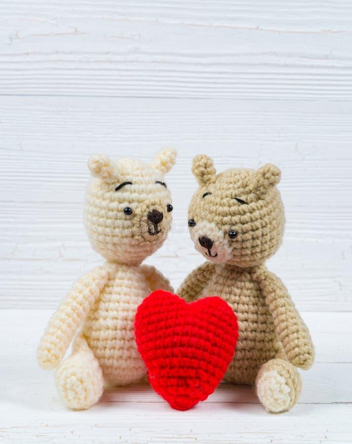 L'orsacchiotto delle coppie con cuore rosso lavora all'uncinetto tricottare fatto a mano su wh fotografia stock libera da diritti