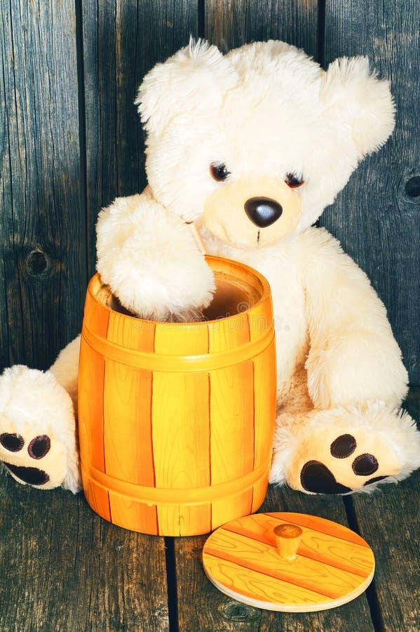 L'orsacchiotto molle bianco riguarda un fondo di legno immagine stock