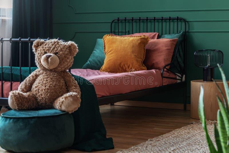L'orsacchiotto riguarda il pouf di verde smeraldo del velluto nell'interno alla moda della camera da letto dell'adolescente con l fotografia stock libera da diritti