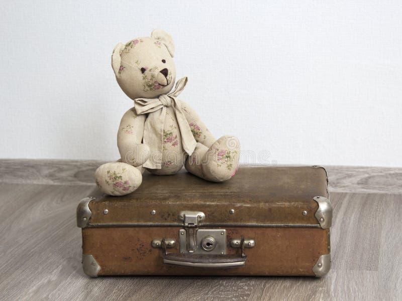 L'orsacchiotto riguarda una vecchia valigia di cuoio fotografia stock