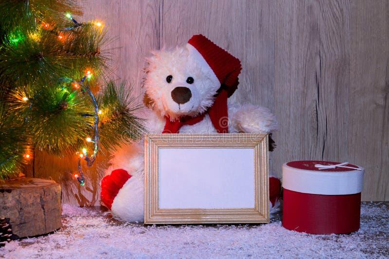 L'orso di Natale, del nuovo anno che si siede sotto un albero di abete con i modelli di una struttura di legno per una foto o tes fotografie stock libere da diritti