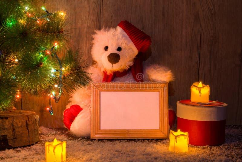 L'orso di Natale, del nuovo anno che si siede sotto un albero di abete con i modelli di una struttura di legno per una foto o tes immagini stock libere da diritti