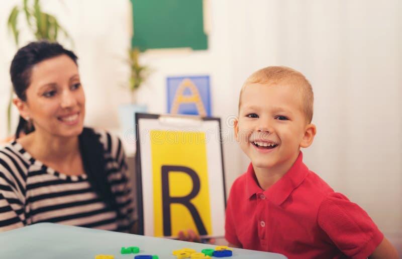 L'orthophoniste enseigne les garçons à dire la lettre photos stock