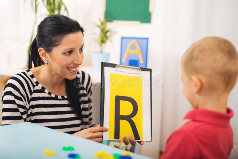 L'orthophoniste enseigne les garçons à dire la lettre R photographie stock