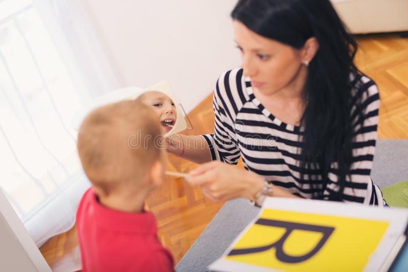 L'orthophoniste enseigne les garçons à dire la lettre R photos libres de droits