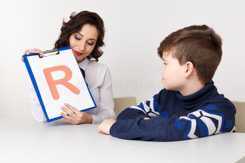 L'orthophoniste enseigne les garçons à dire photographie stock