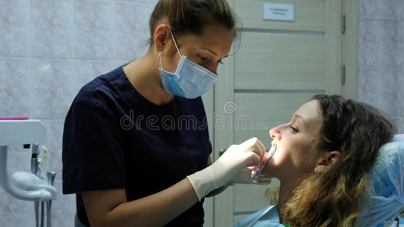 L'ortodontista del dentista mette un fixator dentario affinchè una donna installi un sistema del sostegno Chiamata al dentista fotografia stock