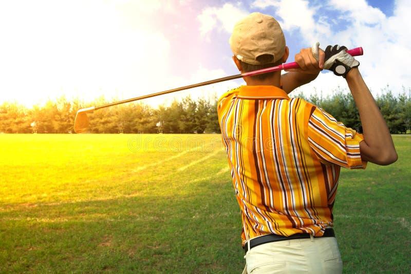 L'oscillation de coup de golf de joueur d'hommes de golfeurs a tiré sur le cours du lever de soleil images stock