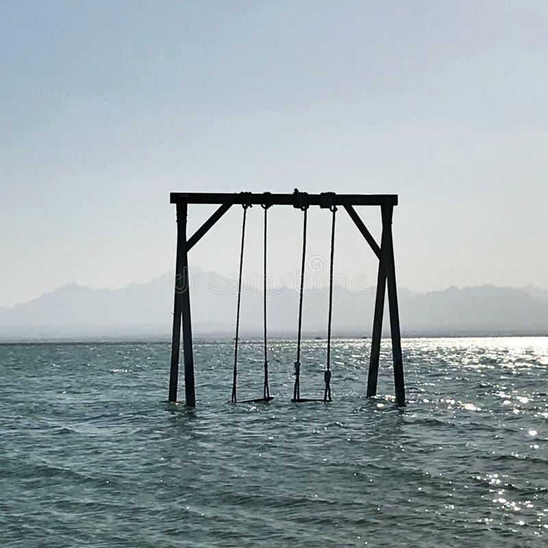 L'oscillation des enfants en bois se tient en mer calme bleue sous le ciel propre ouvert photo libre de droits