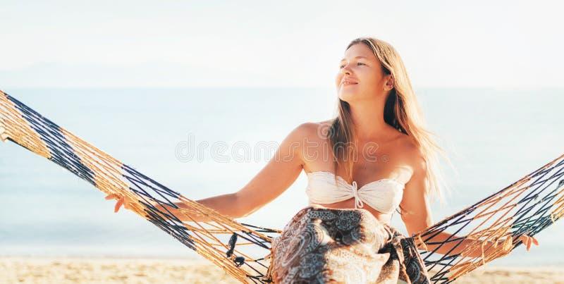 L'oscillation femelle de sourire heureuse dans l'hamac s'est articulée entre les palmiers sur le côté de mer image stock