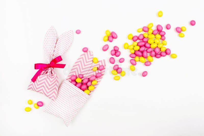 L'ossequio del coniglietto insacca con le caramelle rosa e gialle su fondo bianco fotografie stock libere da diritti