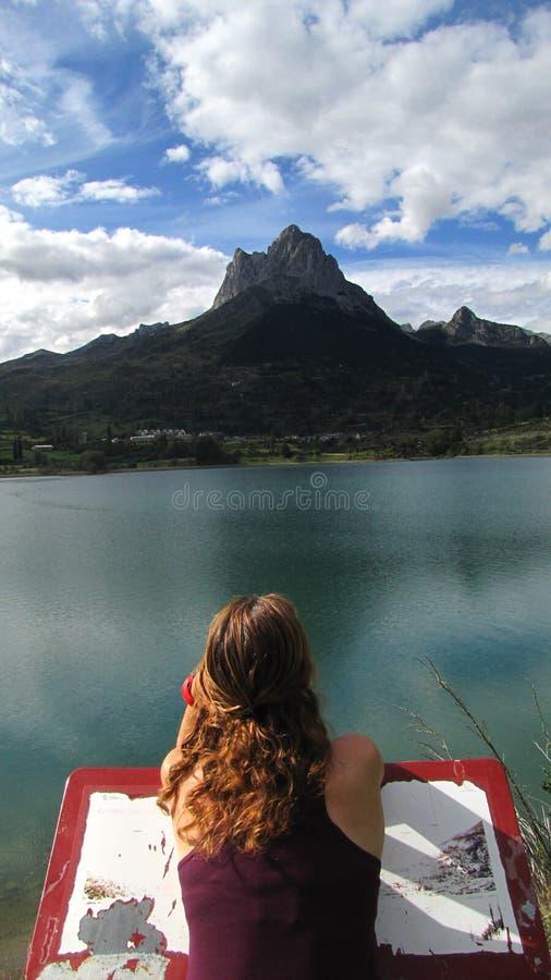 L'osservazione della ragazza ha assorbito il lago ed il picco di montagna fotografia stock libera da diritti
