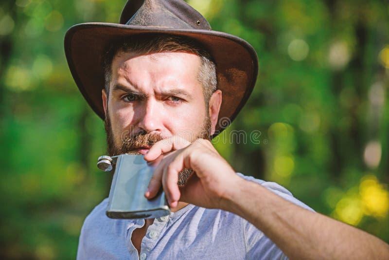 L'ouest sauvage est son coeur Camper et augmenter m?le m?r avec de l'alcool brutal de boissons de regard du flacon Homme barbu da image stock