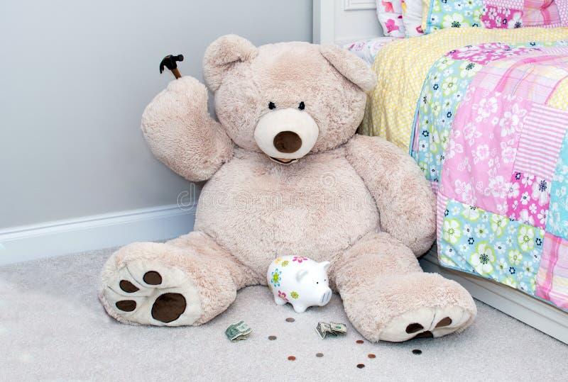 L'ours économe avec le marteau essaye de casser sa banque image libre de droits