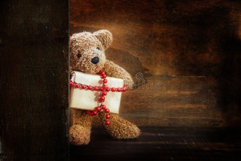 L'ours de nounours apporte un cadeau de Noël décoré d'une chaîne rouge de boule, fond en bois rustique foncé avec l'espace de cop photographie stock libre de droits
