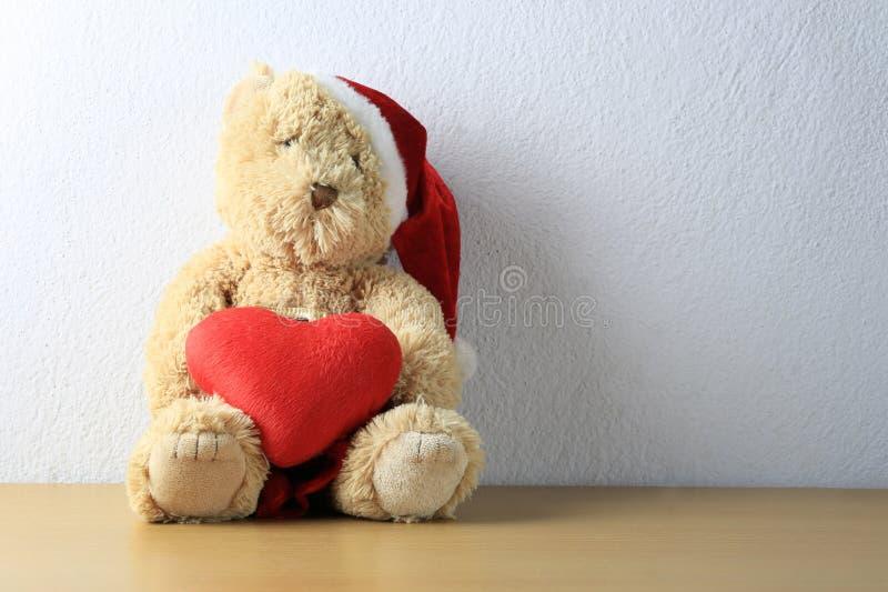 L'ours de nounours avec le coeur rouge se reposent sur un plancher en bois sur le Ba blanc de mur images stock