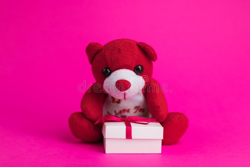 L'ours de nounours de bande dessinée de jouet se repose sur un boîte-cadeau blanc sur un fond rose photographie stock libre de droits