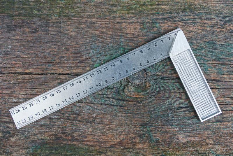 L'outil gris de place en métal se trouve sur un conseil en bois photographie stock libre de droits
