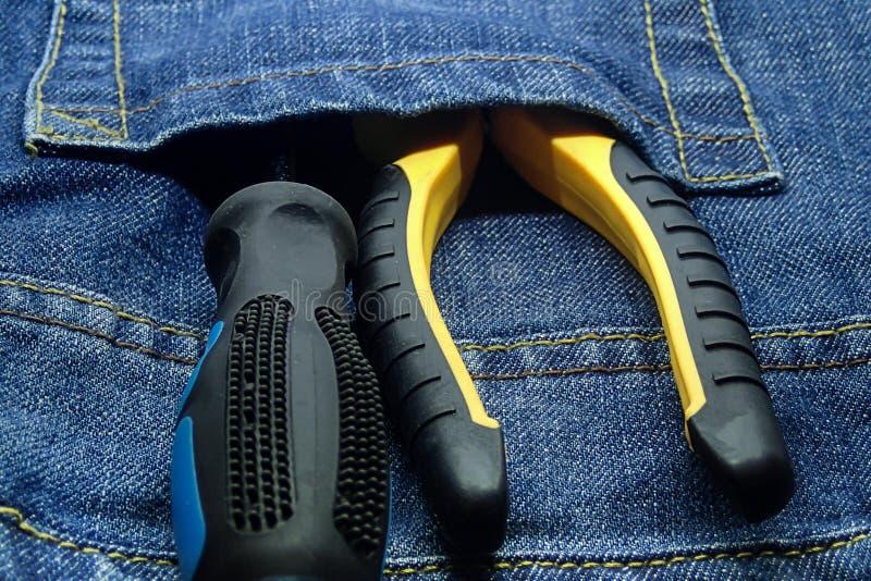 L'outil réglé dans des jeans empochent des pinces de tournevis que le caoutchouc manipule les outils de bricolage en gros plan de photos stock