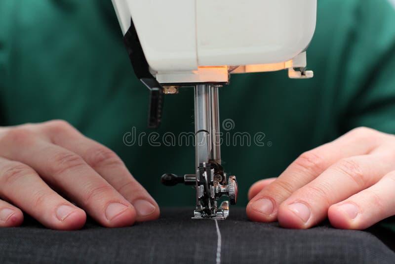 L'ouvrière couturière en gros plan remet travailler à la machine à coudre à la maison Processus de couture mains de femme derrièr photographie stock