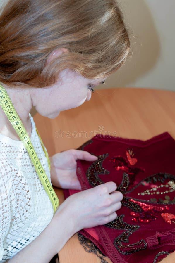 L'ouvrière couturière s'asseyant à la table et brode le gilet rouge avec des perles dans le studio image libre de droits