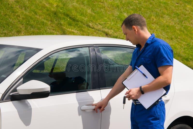 L'ouvrier d'entretien dans le costume bleu, inspecte la voiture photos stock