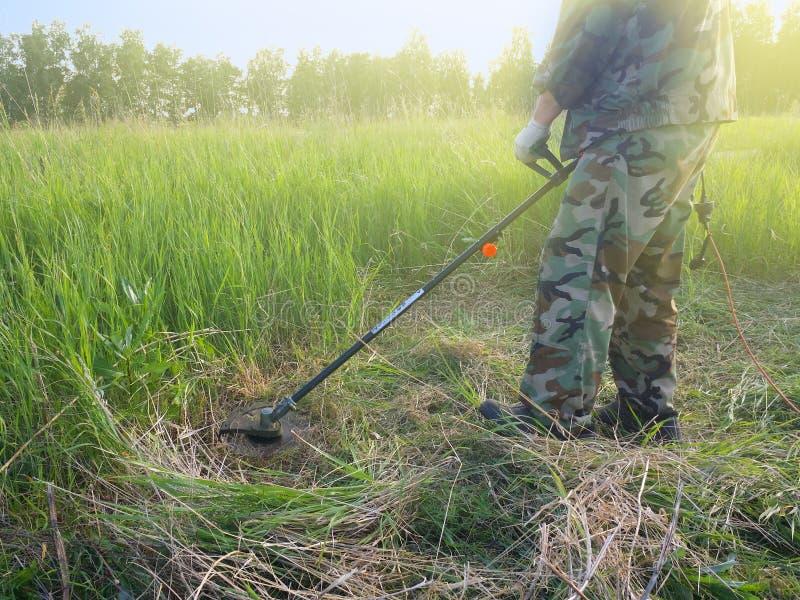 L'ouvrier fauchent la haute herbe avec la tondeuse à gazon électrique photo libre de droits