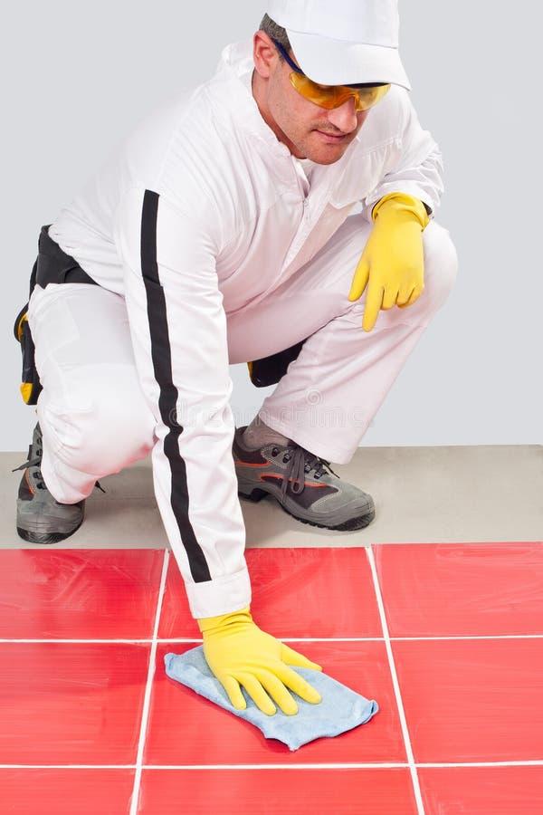 L'ouvrier nettoie les joints blancs photos stock