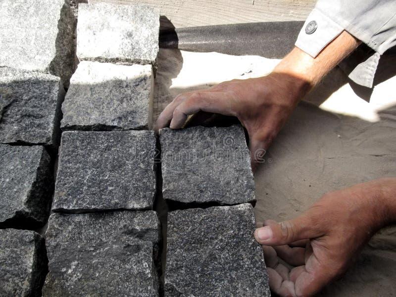 L'ouvrier pave les pavés gris des pavés de granit photos libres de droits