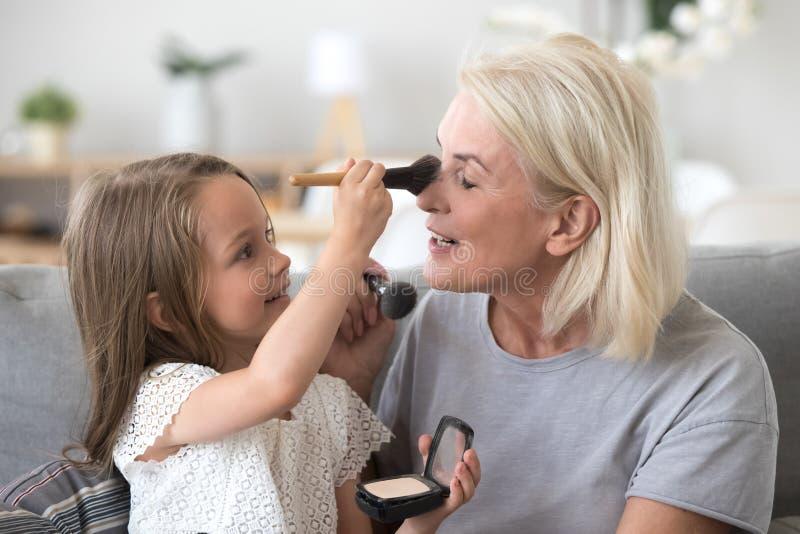 L'petit-enfant et la grand-maman ont l'amusement ensemble à la maison photographie stock libre de droits