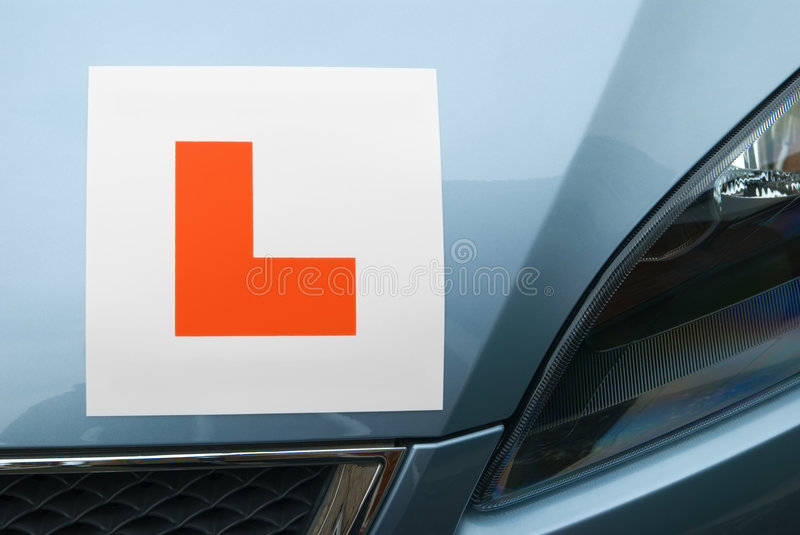 L Plate On Car Hood. Red Learner Driver Symbol on a Car Hood with Blue Metallic Paint stock images
