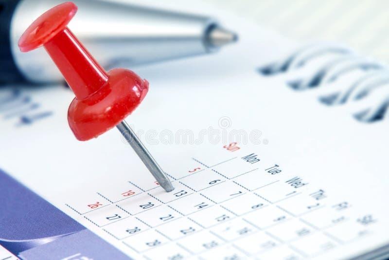 L'a pressione rosso alla pagina del calendario per ricorda a e vigilia importante segnata fotografia stock libera da diritti
