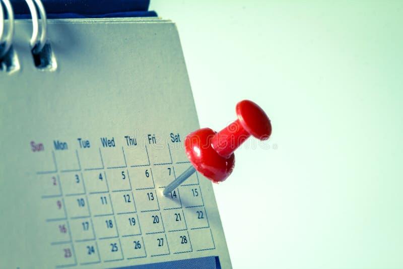 L'a pressione rosso alla pagina del calendario per ricorda a e vigilia importante segnata immagine stock