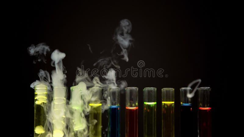 L?quidos multicolores en los tubos de ensayo que emiten humo en el laboratorio oscuro, narc?tico fotografía de archivo libre de regalías