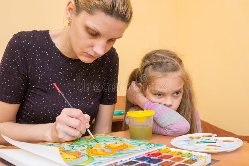 L'ragazza-artista attinge i colori di carta accanto ad una bambina con uno sguardo annoiato fotografia stock