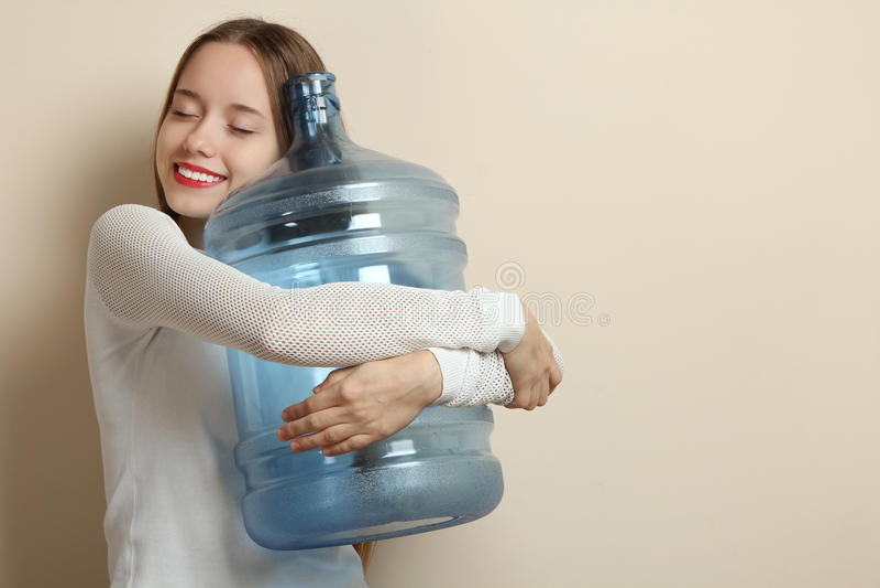 L ragazza che abbraccia una grande bottiglia di acqua immagine stock