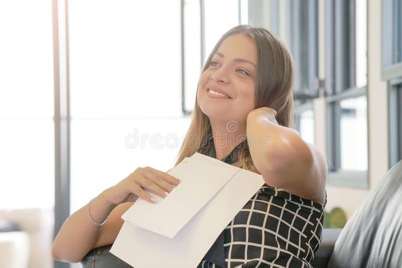 L?s- goda nyheter f?r lycklig entrepren?rkvinna i en bokstav p? soffan arkivbild